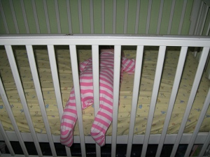 Rosalie asleep with her legs out of the crib