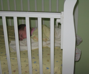 Rosalie w/ her legs out of the crib
